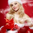 Winter portrait of a santa woman with a christmas gift — Stock Photo #14448875