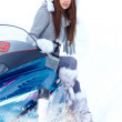 Stock Photo: Smiling young woman riding a snowmobile