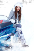 Smiling young woman riding a snowmobile — Stock Photo