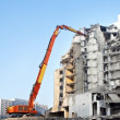 Partly demolished office building with demolition cranes - Stock Photo