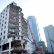 Stock Photo: Partly demolished office building with demolition cranes
