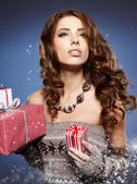 Sexy girl smiles and holding a gift in magic packing — Stock Photo