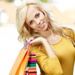 Beautiful woman in town holding shopping bags  — Stockfoto