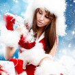 Winter portrait of a santa woman with a christmas gift — Stock Photo #16627291