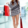 Smiling girl with shopping bags in shop — Stock Photo #16636881