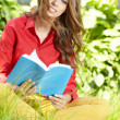 Beautiful girl with book in the spring park - Stock Photo