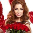 Young beautiful woman smelling a bunch of red roses - Stock Photo