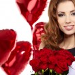 Young beautiful woman smelling a bunch of red roses - Photo