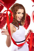 Beautiful fashion woman in red posing with red ballons — Stock Photo