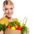 Woman holding a shopping bag full of groceries, mango, salad, r — Stock Photo #19053241