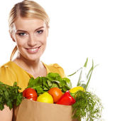 Woman holding a shopping bag full of groceries, mango, salad, r — Stock Photo