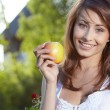 Apple woman. Very beautiful model eating red apple in the park. — Stock Photo #19116697
