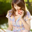 Apple woman. Very beautiful model eating red apple in the park. — Stock Photo #19116821