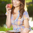 Royalty-Free Stock Photo: Apple woman. Very beautiful  model eating red apple in the park.