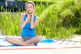 Brunette girl doing yoga exercises by pool — Stock Photo