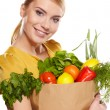 Beautiful young woman with vegetables and fruits in shopping bag — Stok fotoğraf