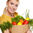 Beautiful young woman with vegetables and fruits in shopping bag - Stock Photo