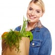 Portrait of happy young woman holding a shopping bag full of gro — Stock Photo