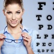 Woman with  trendy glasses on the background of eye test chart - Stok fotoğraf