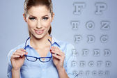 Woman with trendy glasses on the background of eye test chart — Stock Photo
