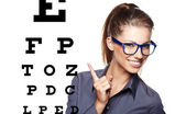 Woman with blue trendy glasses on the background of eye test cha — Stock Photo
