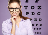 Beautiful woman with trendy glasses on the background of eye te — Stock Photo