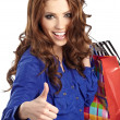 Woman standing with shopping paper bags and showing OK by hand. - Stockfoto