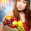 Young woman holding a grocery bag full of fresh and healthy food — Stok fotoğraf