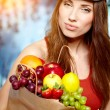 Young woman holding a grocery bag full of fresh and healthy food — Foto Stock