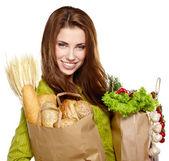 Young woman holding a grocery bag full of fresh and healthy food — Stockfoto