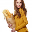 Young woman holding a grocery bag full of bread — Stock Photo #21342905