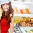 Young woman holding a grocery bag full of bread — Stock Photo #21350335