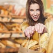 Young woman holding a grocery bag full of bread — Stock Photo #21350377