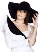 Fashionable woman in a hat posing in light background — Stock Photo
