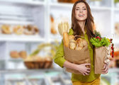 Young woman holding a grocery bag full of bread — Stockfoto