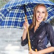 Beautiful blonde woman holding umbrella out in the spring rain — Stock Photo