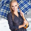 Royalty-Free Stock Photo: Beautiful blonde woman holding umbrella out in the spring rain