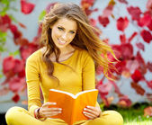 Beautiful girl with book in the spring park — Stock Photo