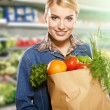 Woman grocery shopping at the local market — Stock Photo #21977345