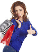 Woman standing with shopping paper bags and showing OK by hand. — Fotografia Stock