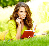 Vacker flicka med bok i höst park — Stockfoto
