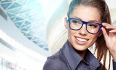 Business woman holding glasses and looking at camera. — Stock Photo