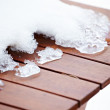 Royalty-Free Stock Photo: Broken melting ice on wooden red painted deck