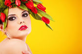 Beauty woman portrait with wreath from flowers on head over yell — Photo
