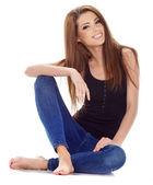 Beautiful brunette woman sitting on the floor . Studio shoot. — Stock Photo