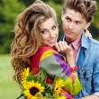 Young couple with sunflowers, outdoors — Stock Photo