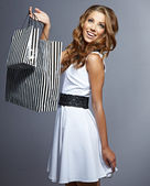 Woman holding shopping bags against a grey background — Stock Photo