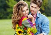 Mladý pár s slunečnice, venku — Stock fotografie
