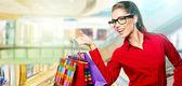 Beautiful shopping woman at a drawn mall — Stock Photo