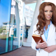 Young businesswoman standing in front of office buildings - Stock Photo